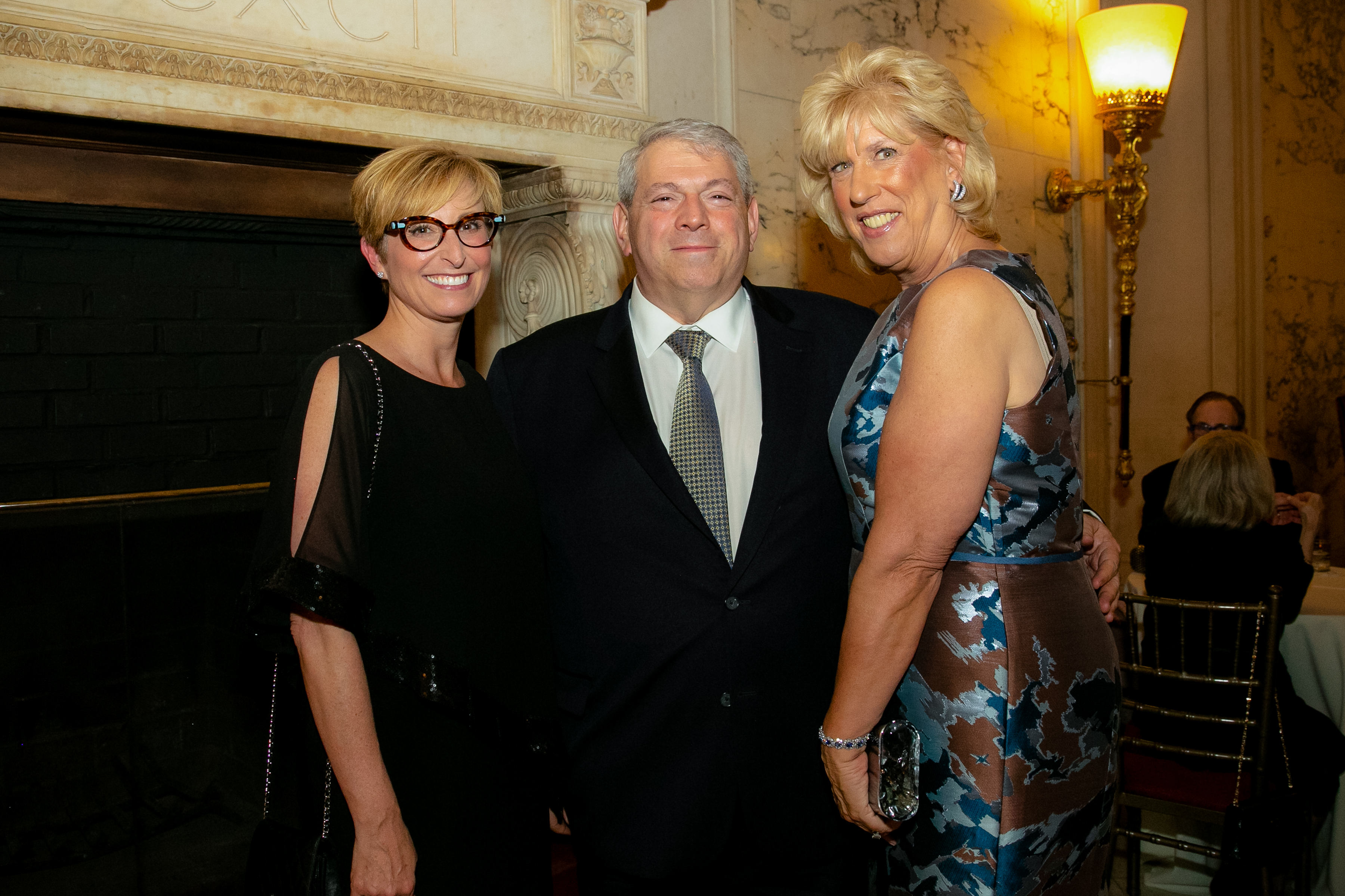Three people standing and smiling in front of a fireplace at 2019 Gala