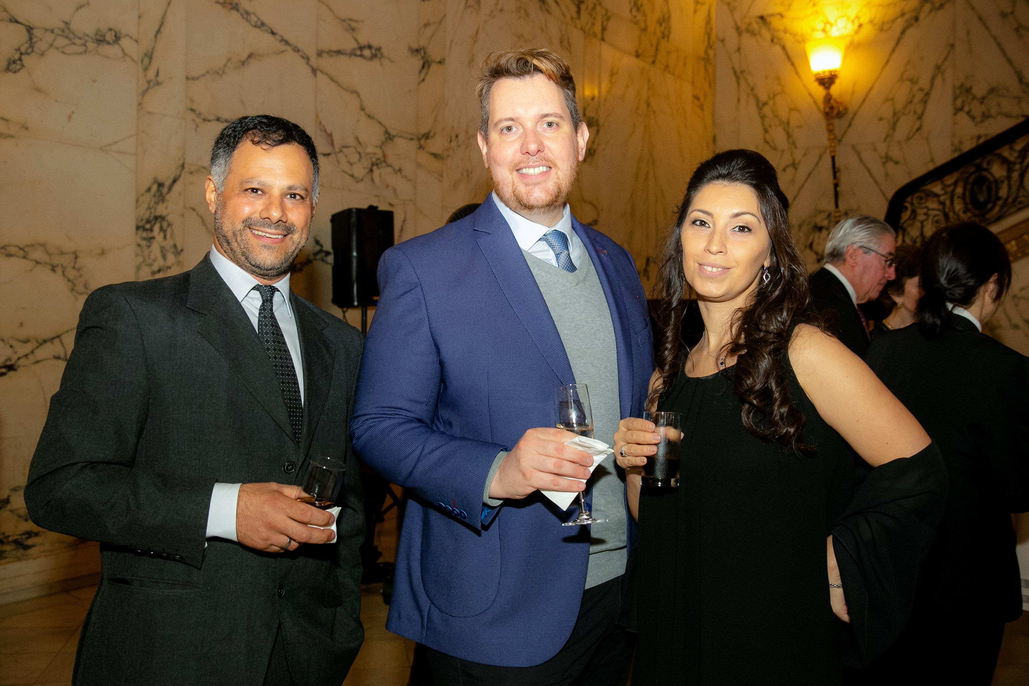 Three people smiling and holding glasses at the 2019 Gala