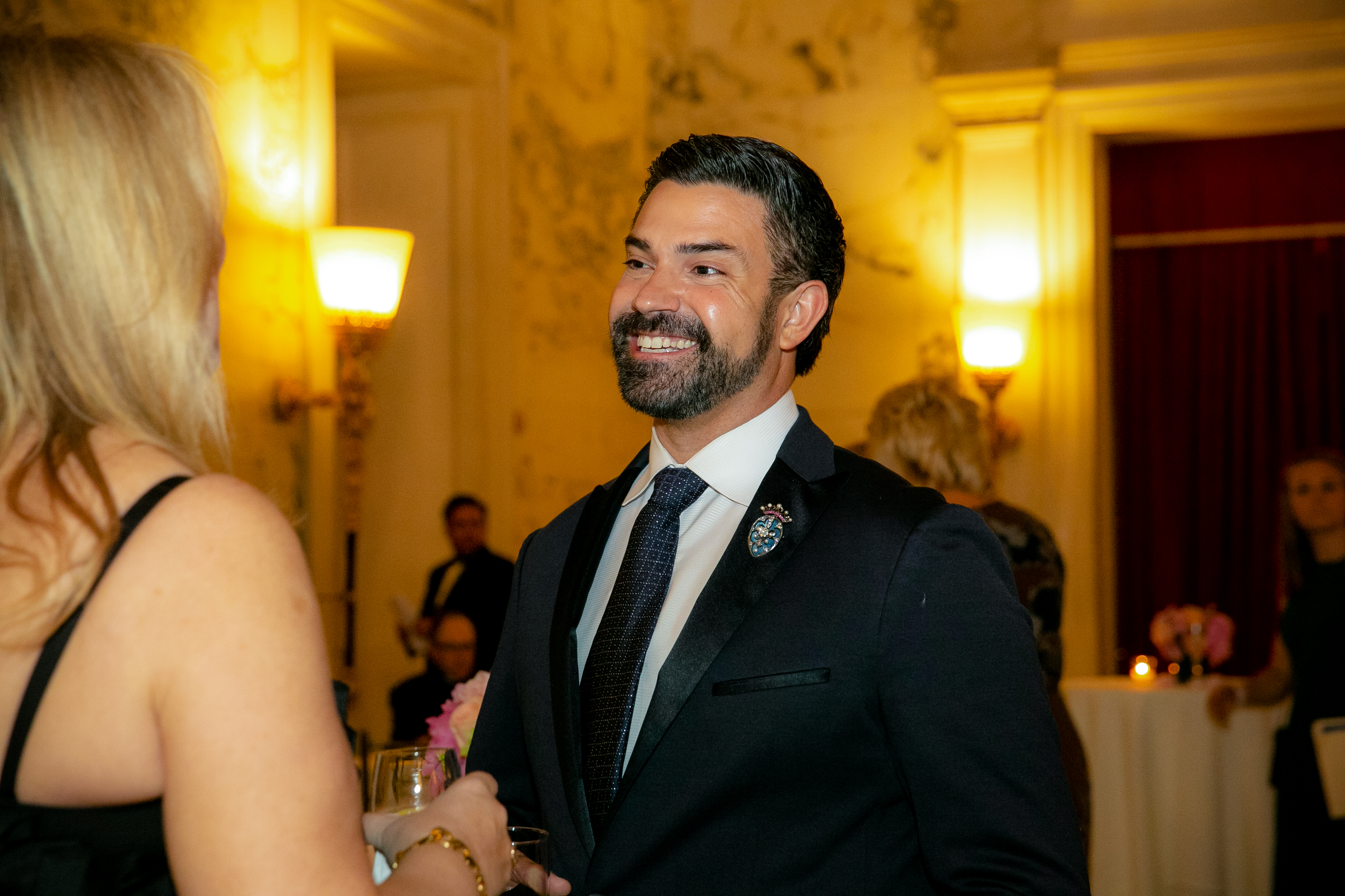 A man with a beard and black suit smiles at a woman at the Gala