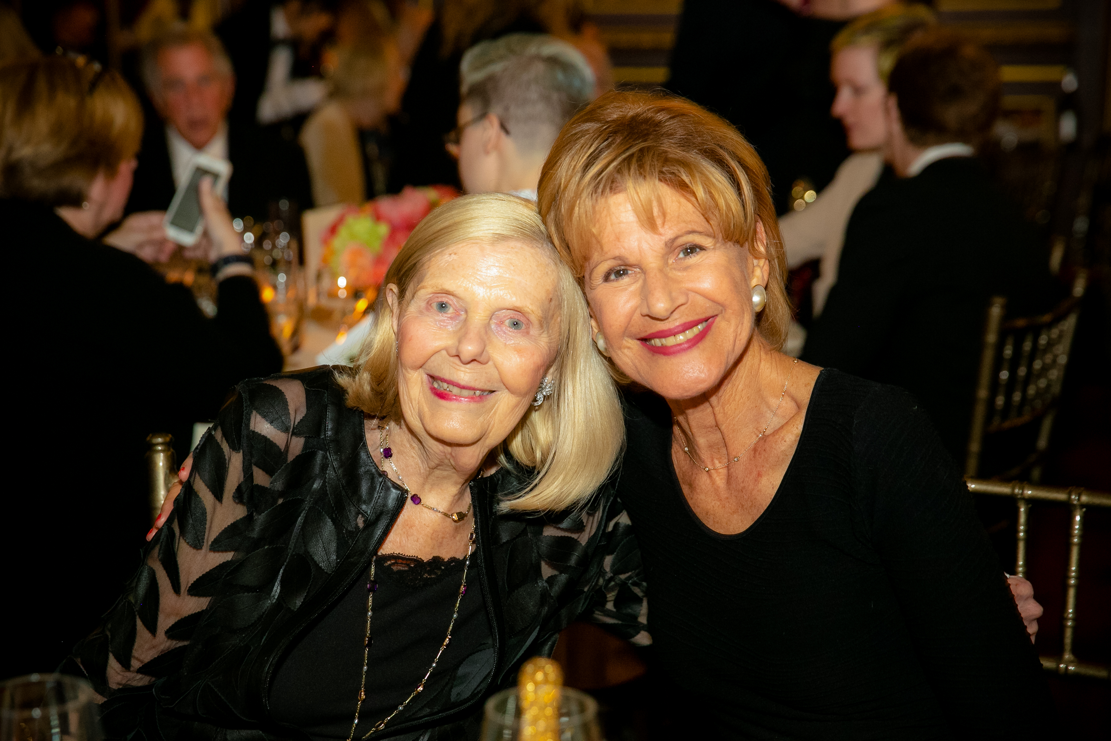 Two women seated side by side smile at the camera during 2019 Gala Event