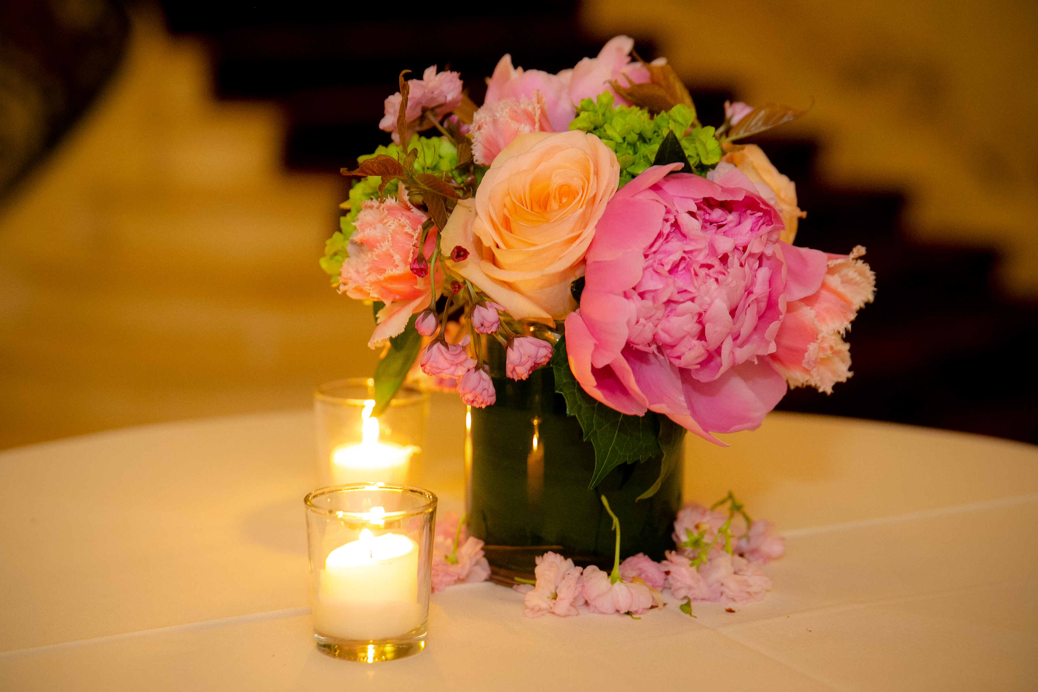 A picture of a floral arrangement with rose, yellow, and pastel colors on a table next to candles