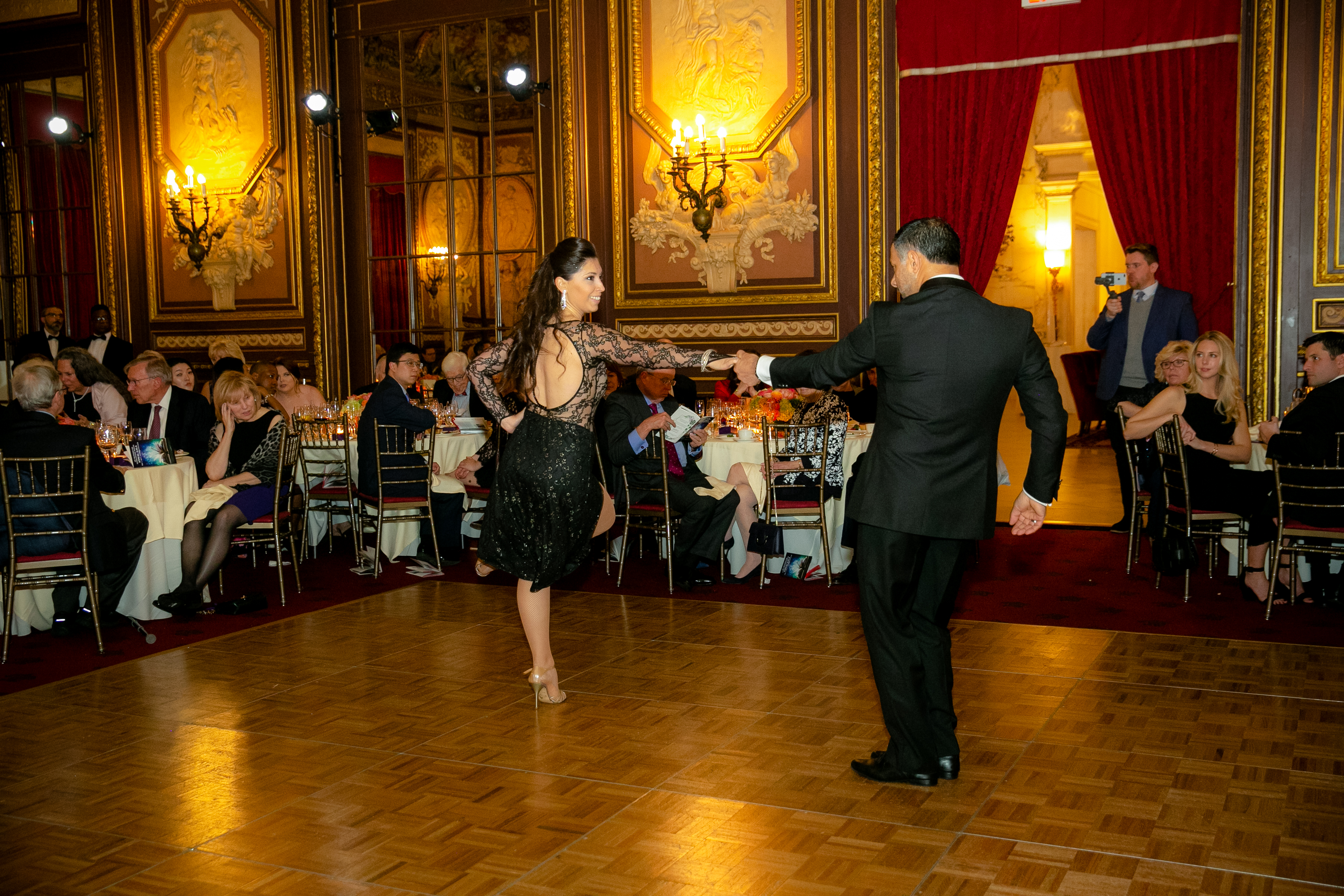 A man and a woman are dancing alone on the ballroom while seated guests watch
