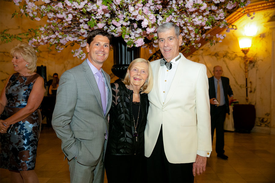 Three people pose under a floral centerpiece at the 2019 Gala Event