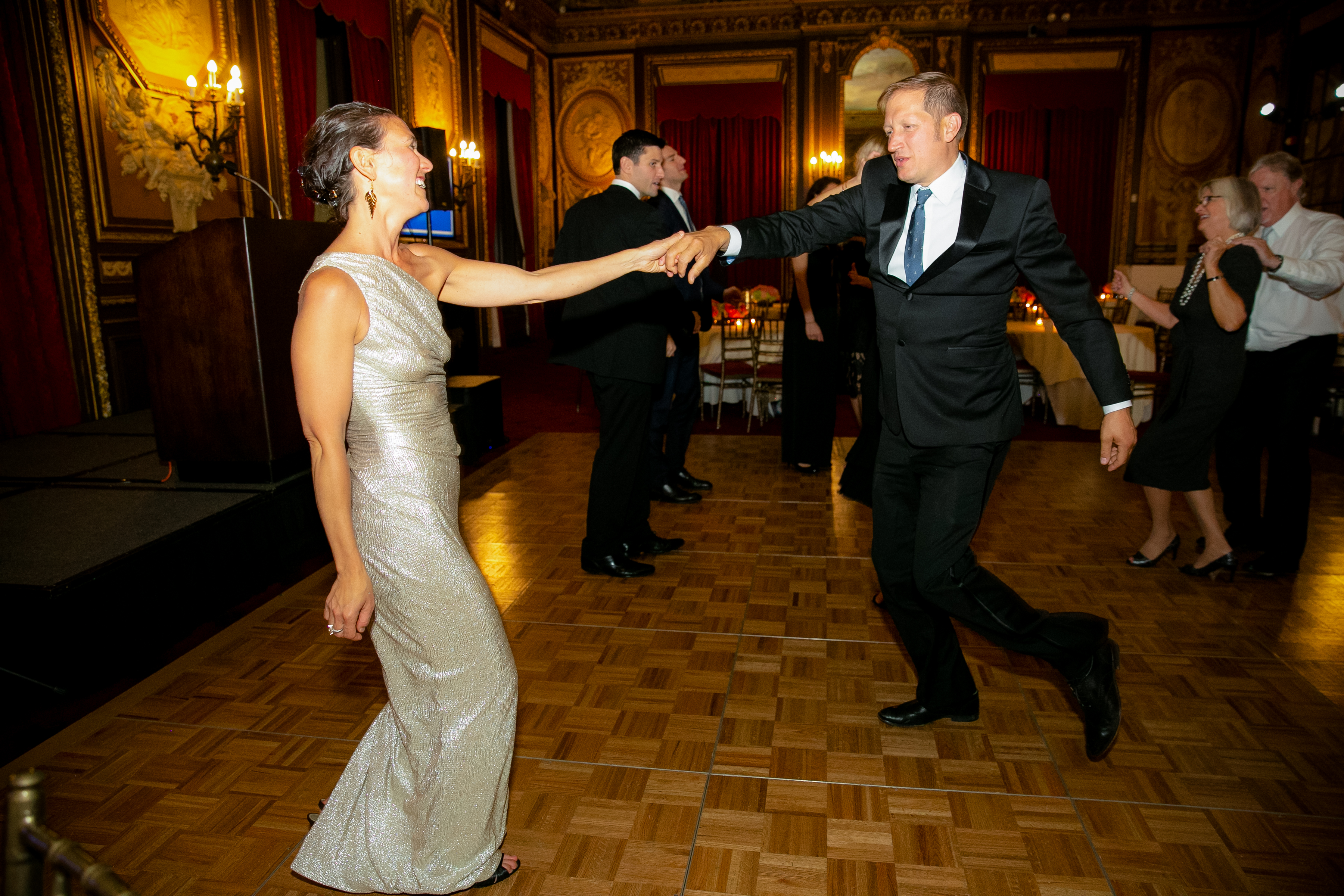 A man in a suit twirls a woman in a silver dress at the 2019 Gala