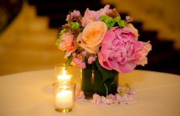 A vase of roses with 2 candles on the table